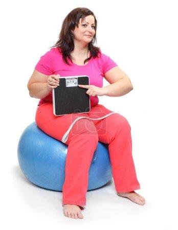 Photo pour Femme en surpoids avec peseuse, ruban à mesurer, assise sur une boule sur fond blanc - image libre de droit