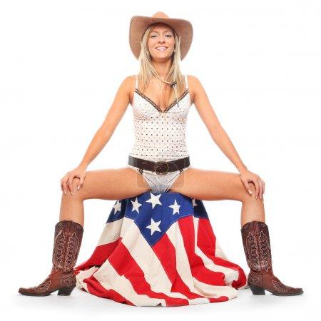 Photo pour Cowboy girl assis sur un drapeau américain. Isolé sur blanc - image libre de droit
