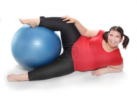 Overweight woman exercising with ball