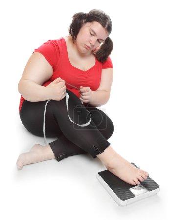 Photo pour Femme en surpoids mesurer son ventre par mètre-bâton sur une machine de pesage . - image libre de droit