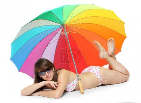 Young woman in swimsuit resting under a beach umbrella.