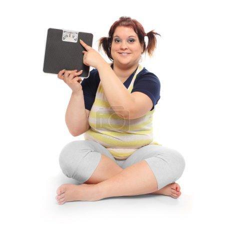 Photo pour Femme en surpoids avec peseuse sur fond blanc - image libre de droit