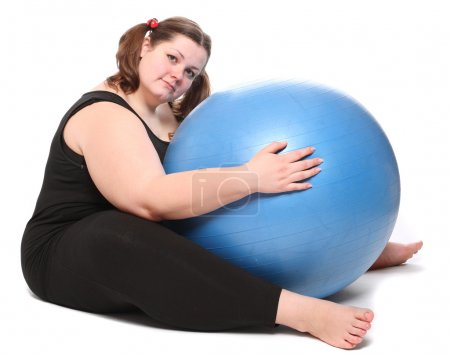Shot of a happy overweight young woman with blue ball on a white background.