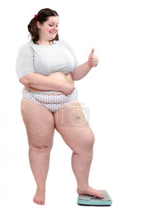 Happy overweight woman measure her waist belly by metre-stick on a weighing machine.