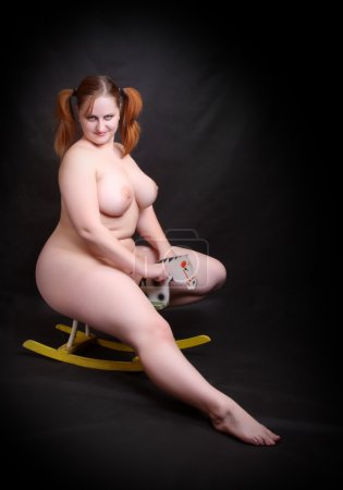 Happy overweight woman riding on a little hobby horse.