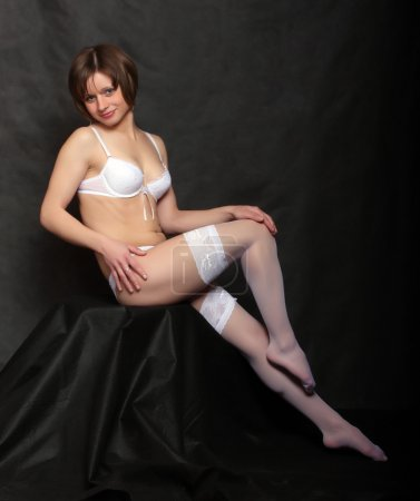 Flirty girl with long slim legs in white nylons. Vintage style low key photography.