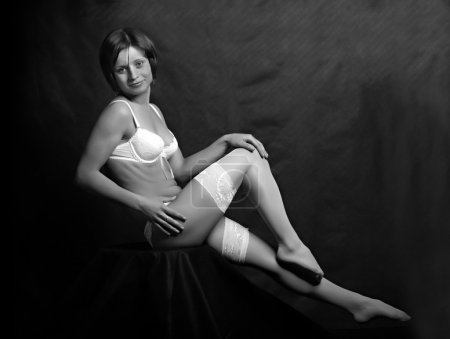 Sitting flirty girl with long slim legs in white nylons. Monochrome low key photography.