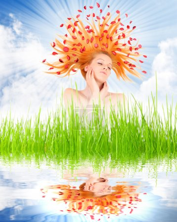 Beautiful woman with flowers on her long hair in fresh spring grass.