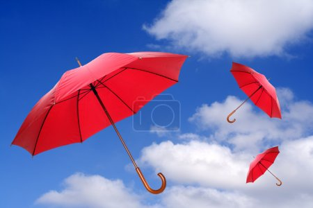 Three red umbrellas flying