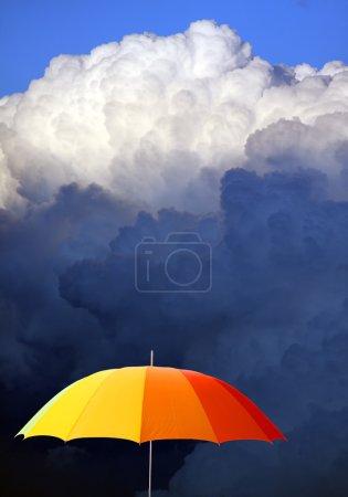 Photo pour Parapluie coloré contre le ciel orageux - image libre de droit