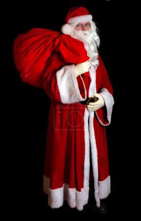 Photo pour Père Noël traditionnel avec un sac sur le dos sur fond noir - image libre de droit