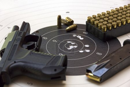 Gun and ammunition over bullseye score