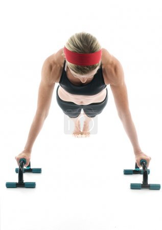 Woman exercising doing push up with fitness push up bar front view