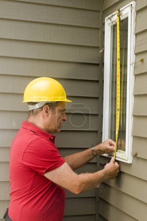 Carpenter measuring window repair