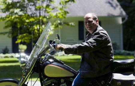 Photo pour Patriotique moyen âge senior homme sur grande moto à la banlieue maison portant manteau protecteur équitation en cuir - image libre de droit