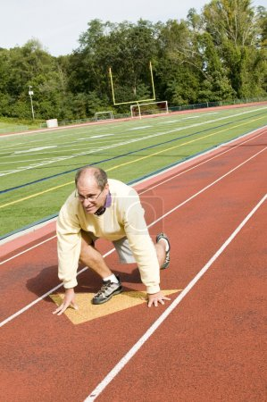 Middle age senior man exercising running on sports field and run