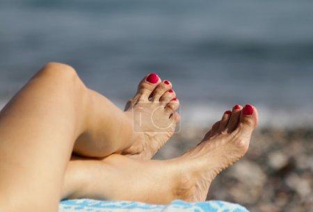Photo pour Belle femme aux orteils pédicurés bronzant sur la plage méditerranéenne . - image libre de droit
