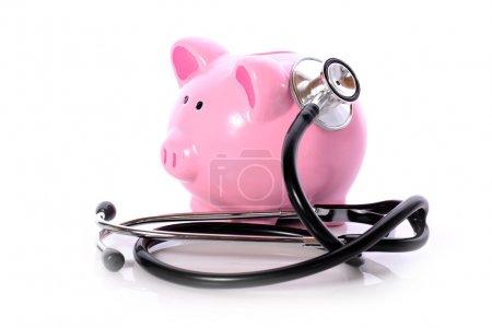 Foto de Hucha con estetoscopio aislado en blanco concepto para chequeo financiero o ahorro de los costos del seguro médicos - Imagen libre de derechos