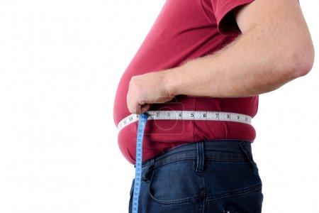 Photo for Side profile of an over weight man measuring stomach - Royalty Free Image