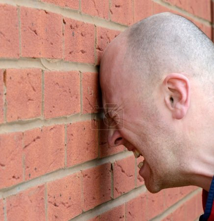 A man banging his head agaist the wall in frustrat...