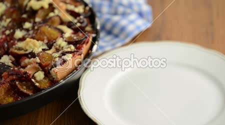 Take a piece of plum cake of crumpet with a cake fork on a plate