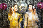 Two beautiful sexy disco women in gold and silver catsuits danci