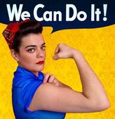 Young woman posing as working girl like the original poster of Rosie the Riveter, year 1943