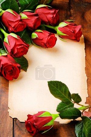 Foto de Marco romántico con rosas rojas y papel vintage - Imagen libre de derechos