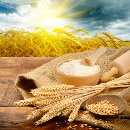 Photo for Organic ingredients for bread preparation with golden sunrise on background - Royalty Free Image