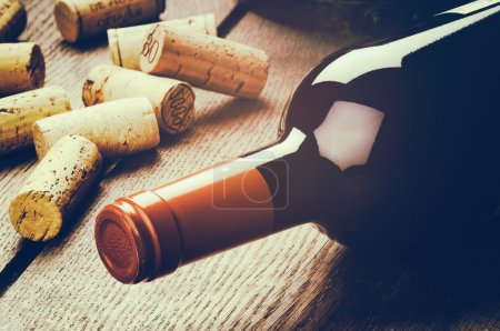 Photo for Bottle of red wine and corks on wooden table - Royalty Free Image