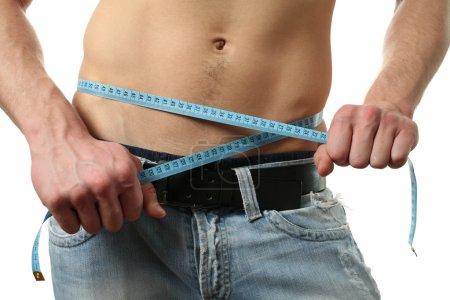 Photo pour Homme musclé mesurant sa taille au mètre isolé sur blanc - image libre de droit