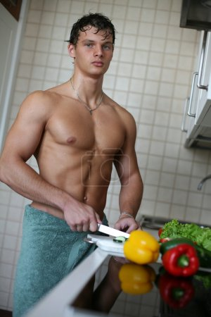 Photo for Young muscular sexy man preparing salad at the kitchen - Royalty Free Image
