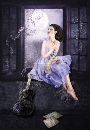 Photo pour La jeune fille assise sur un rebord de fenêtre et rêve au clair de lune - image libre de droit