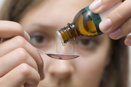 Foto de Esencia herbal goteo de un frasco con una cuchara - Imagen libre de derechos