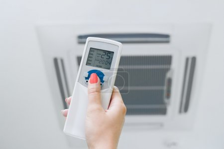 Photo for Hand is holding a remote control of air conditioner - Royalty Free Image
