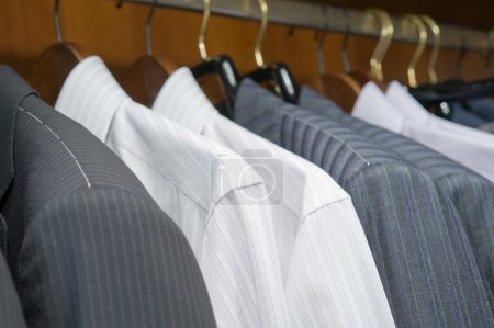 Hangers with jackets and shirts of man's clothing
