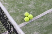 Tennis or paddle balls on synthetic grass of paddle court