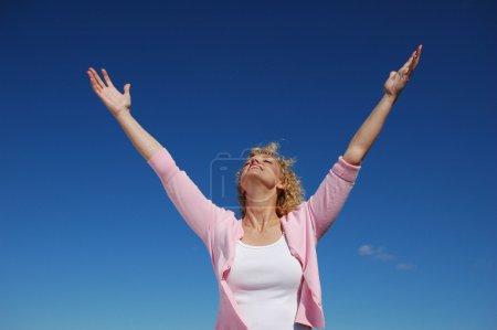 Photo pour Femme avec les bras grands ouverts contre un ciel bleu - image libre de droit