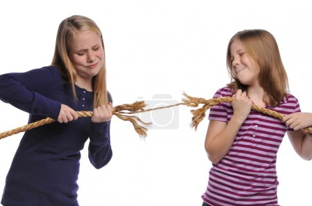 Photo for Two girls fighting over a rope isolated on a white background - Royalty Free Image