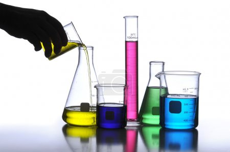 Photo for Laboratory Glassware containing different colored liquids against a neutral background - Royalty Free Image