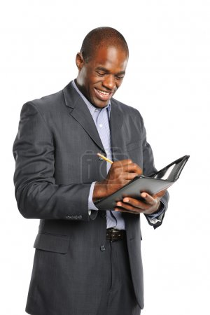 Young smiling black businessman taking notes
