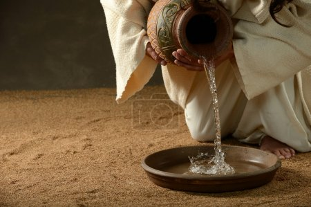 Foto de Jesus pouring water from a jug (with copyspace for text) - Imagen libre de derechos