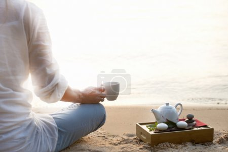 Photo for Woman meditating and drinking tea on beach - Royalty Free Image
