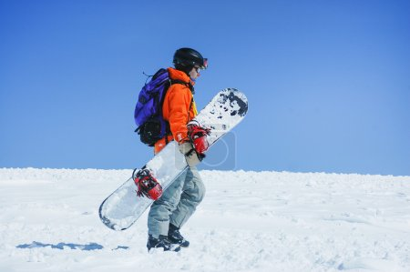 Snowboarder walking at the mountains