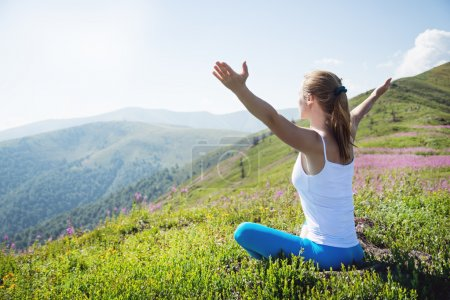 Photo for Young woman meditate on the top of mountain in sunrise time - Royalty Free Image