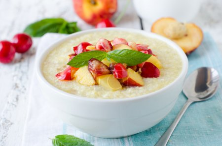 Milk porridge with peaches and cherries