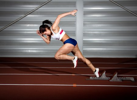 Photo for Woman sprinter leaps from starting block. - Royalty Free Image