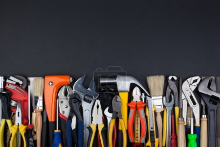 Photo for Work tools lined up in a straight line on black background. - Royalty Free Image