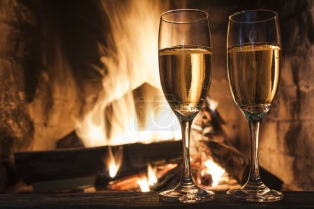 Glasses of champagne in front of fireplace...