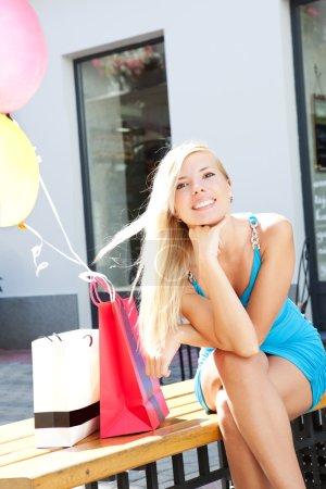 Young beautiful girl relaxing after shopping